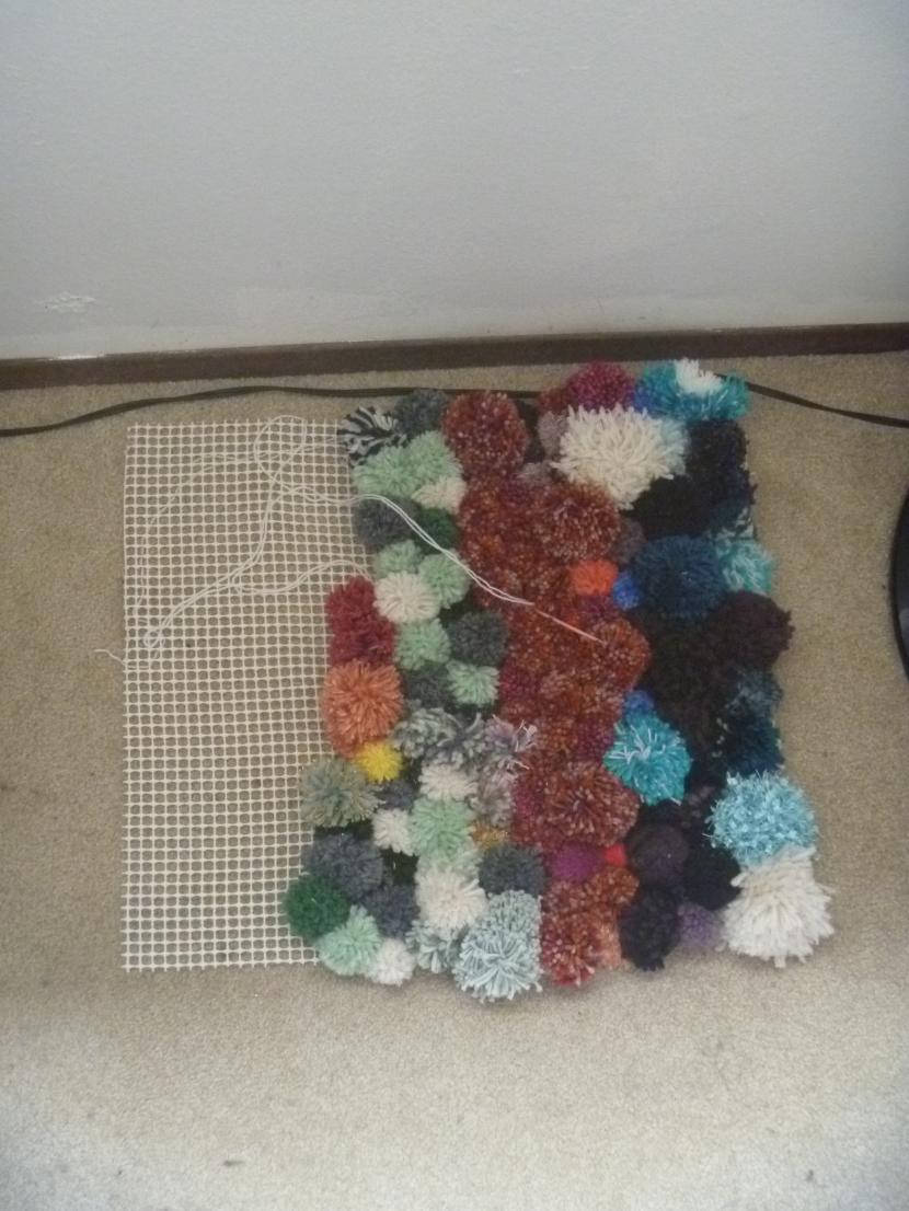 partially done rug of pom poms