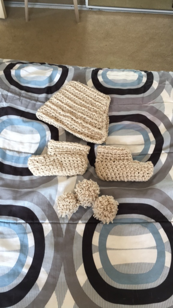 crocheted booties, hat and pom poms