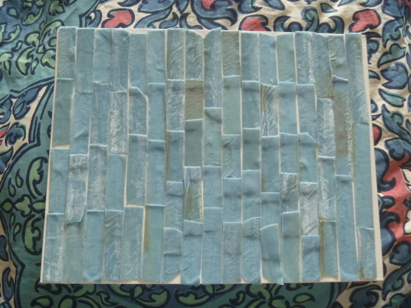 strips of blue velvet ribbon glued onto board