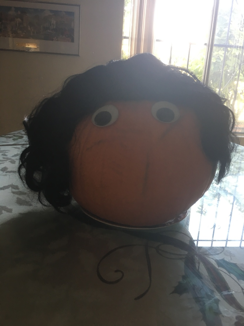 googly eyes and wig on a pumpkin