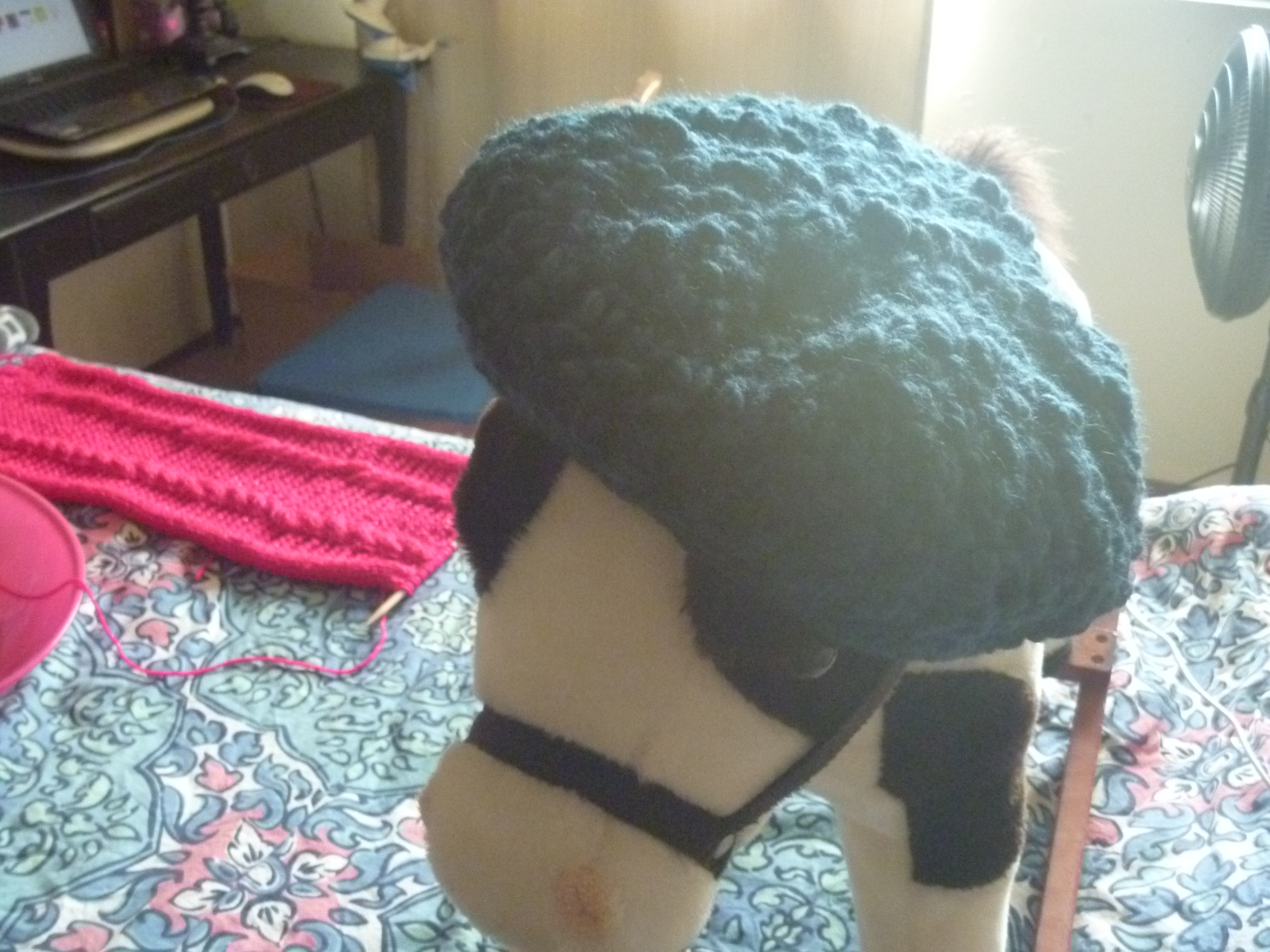 semi-blurry picture of a rocking horse wearing a beanie or beret, with a view of the scarf nearby