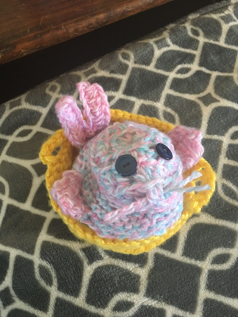 amigurumi seal that looks like a bunny in a yellow basket