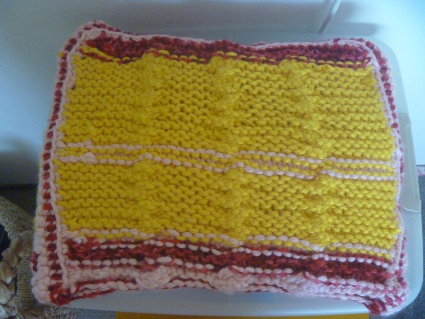 front of knit striped yellow and pink pillow