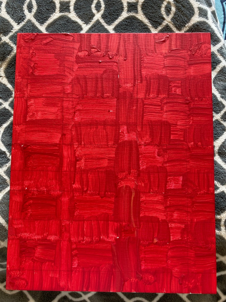 Canvas panel covered in red and yellow variants of paint