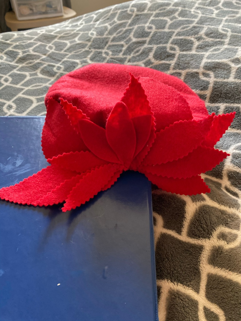 Red felt beret with red cut out embellishments attached in front